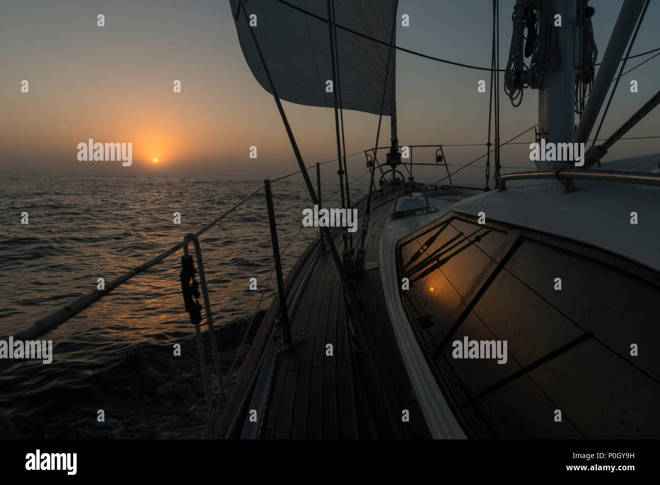 A yacht sailing offshore in light fog at dawn, north of the southern limit for ice, in the North Atlantic north east of Bermuda. - Stock Image