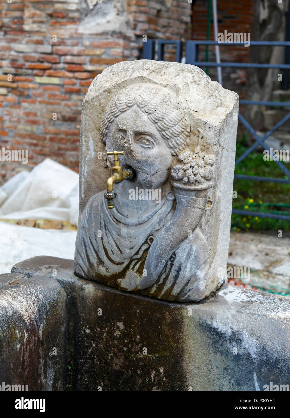 A water tap coming out of the mouth of a stone fountain in the shape of a persons head at the Pompeii Archaeological site, Pompeii, Campania, Italy, - Stock Image