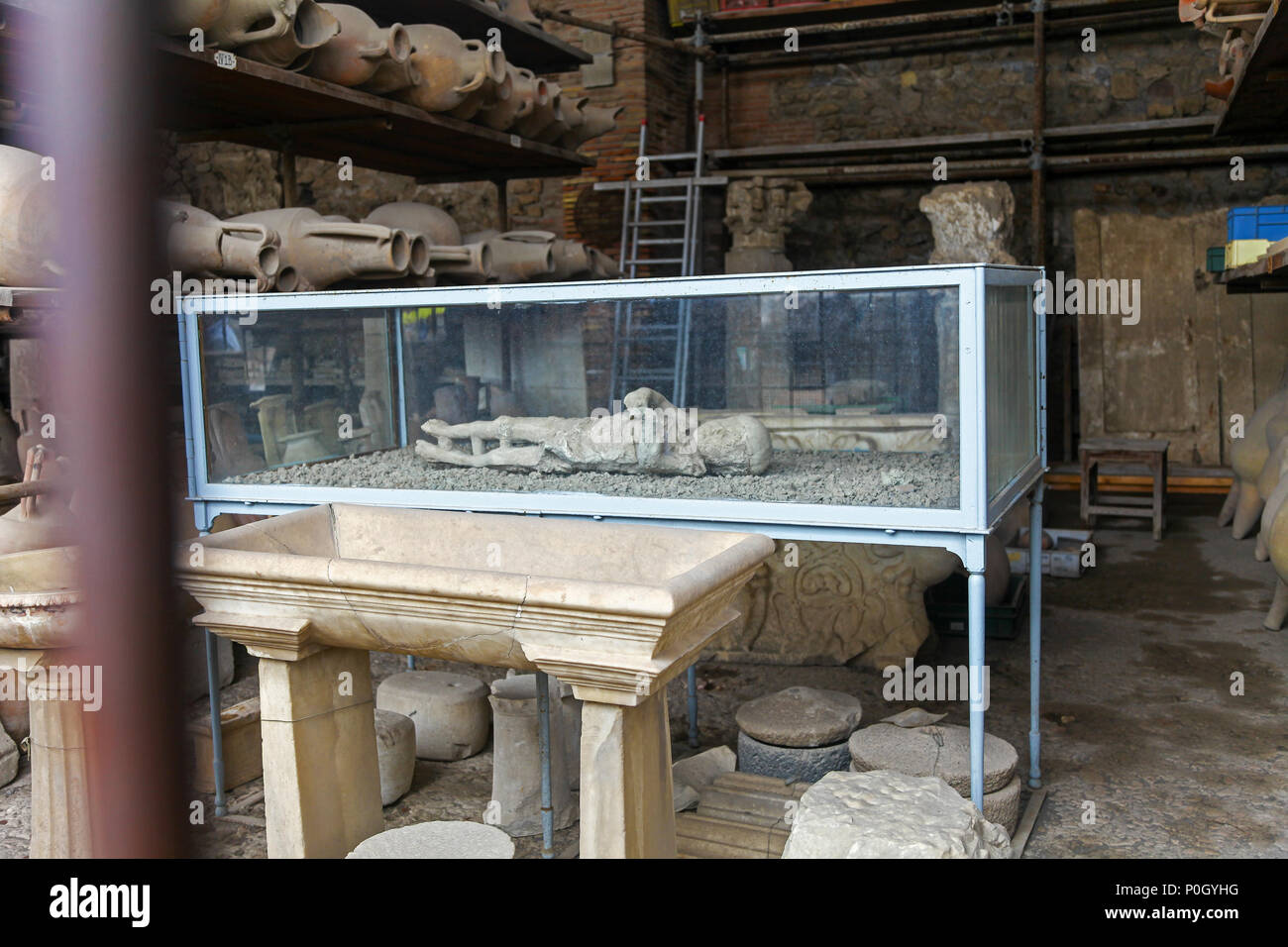 Plaster cast of a small child in a glass case, from the eruption of Vesuvius in AD 79 at the Pompeii Archaeological site, Pompeii, Campania, Italy, - Stock Image