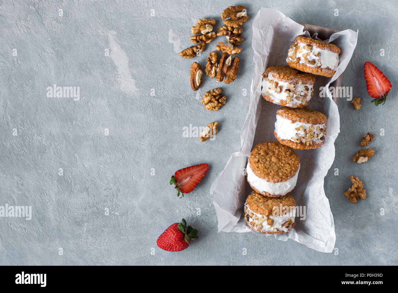 Ice cream sandwiches with nuts and wholegrain cookies. Homemade vanilla ice cream sandwiches on gray concrete background. Stock Photo