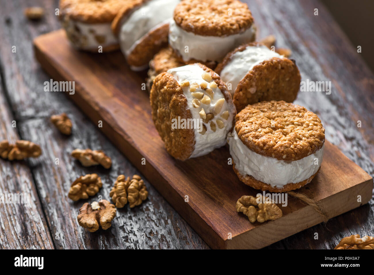 Ice cream sandwiches with nuts and wholegrain cookies. Homemade vanilla ice cream sandwiches on dark wooden background. - Stock Image