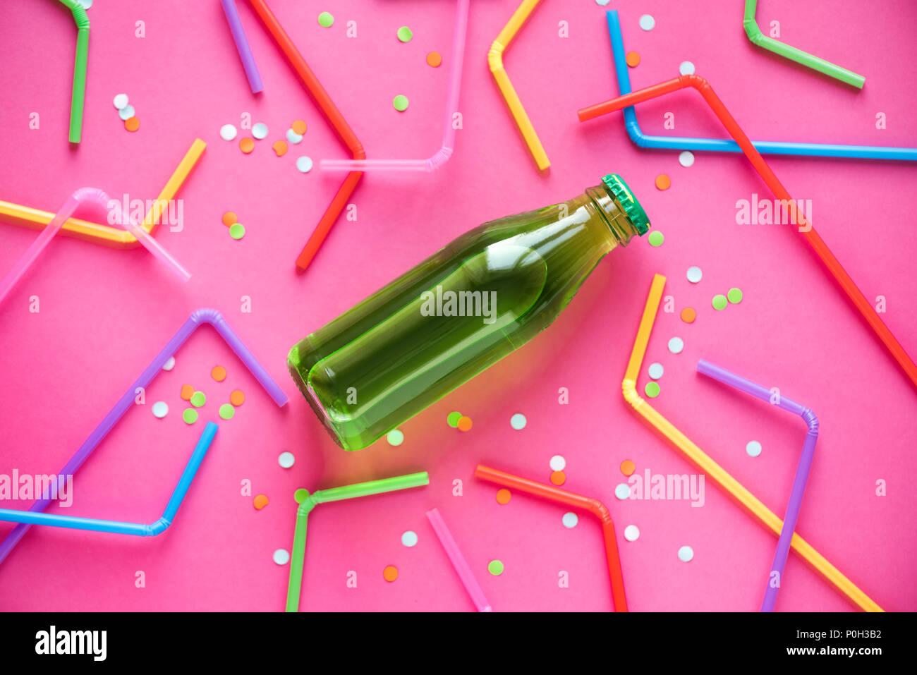 Cold green drink with straws and confetti on bright pink background and copy space for text. Summer party, happy vacation and fun concept, top view. - Stock Image