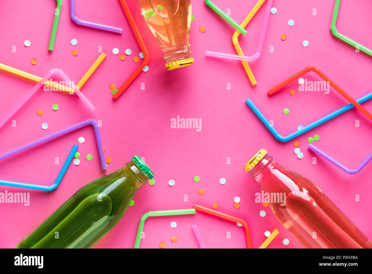 Various cold drinks with straws and confetti on bright pink background and copy space for text. Summer party, happy vacation and fun concept, top view - Stock Image