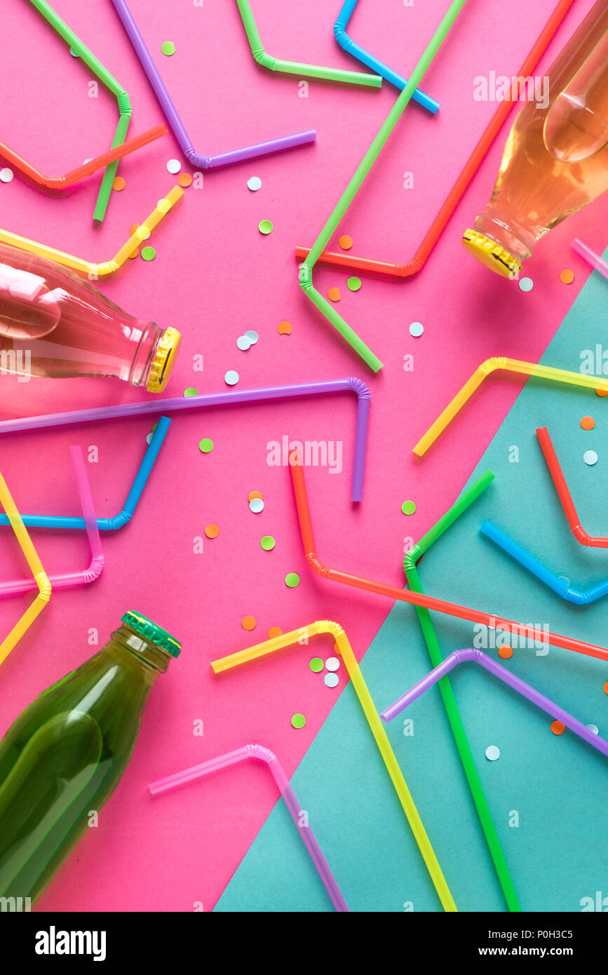 Various cold drinks with straws and confetti on pink and blue background. Summer party, happy vacation and fun concept, top view. - Stock Image