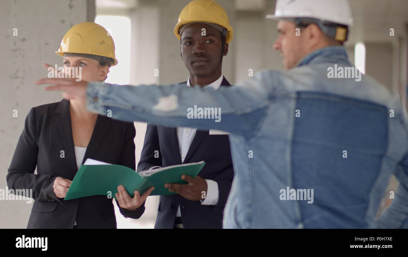 Business people group on meeting and presentation in construction business people group on meeting and presentation in construction site with construction engineer architect and worker looking building model and blueprint malvernweather Images