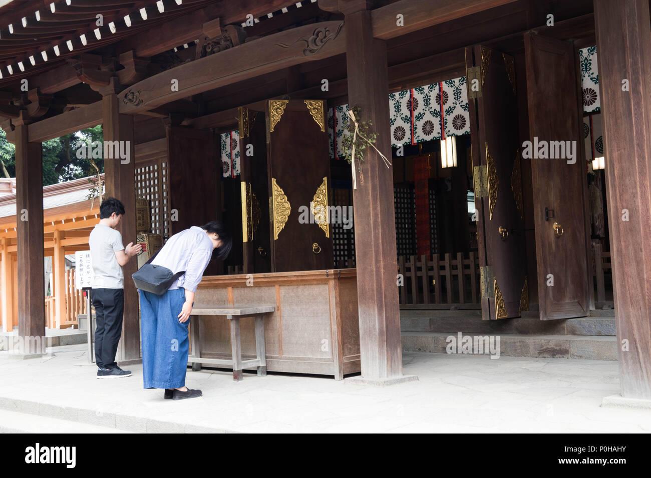 Worshipper bowing in prayer at Hikawa Jinja shrine, Omiya, Saitama, Japan - Stock Image