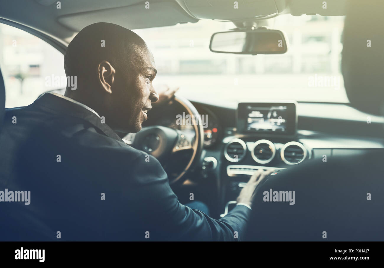 Rearview of a young African businessman changing radio stations while driving through the city streets in his car - Stock Image