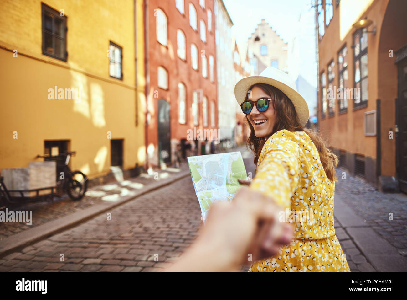 POV of a laughing young woman wearing sunglasses and reading a map while leading another person by the hand through cobblestone city streets - Stock Image