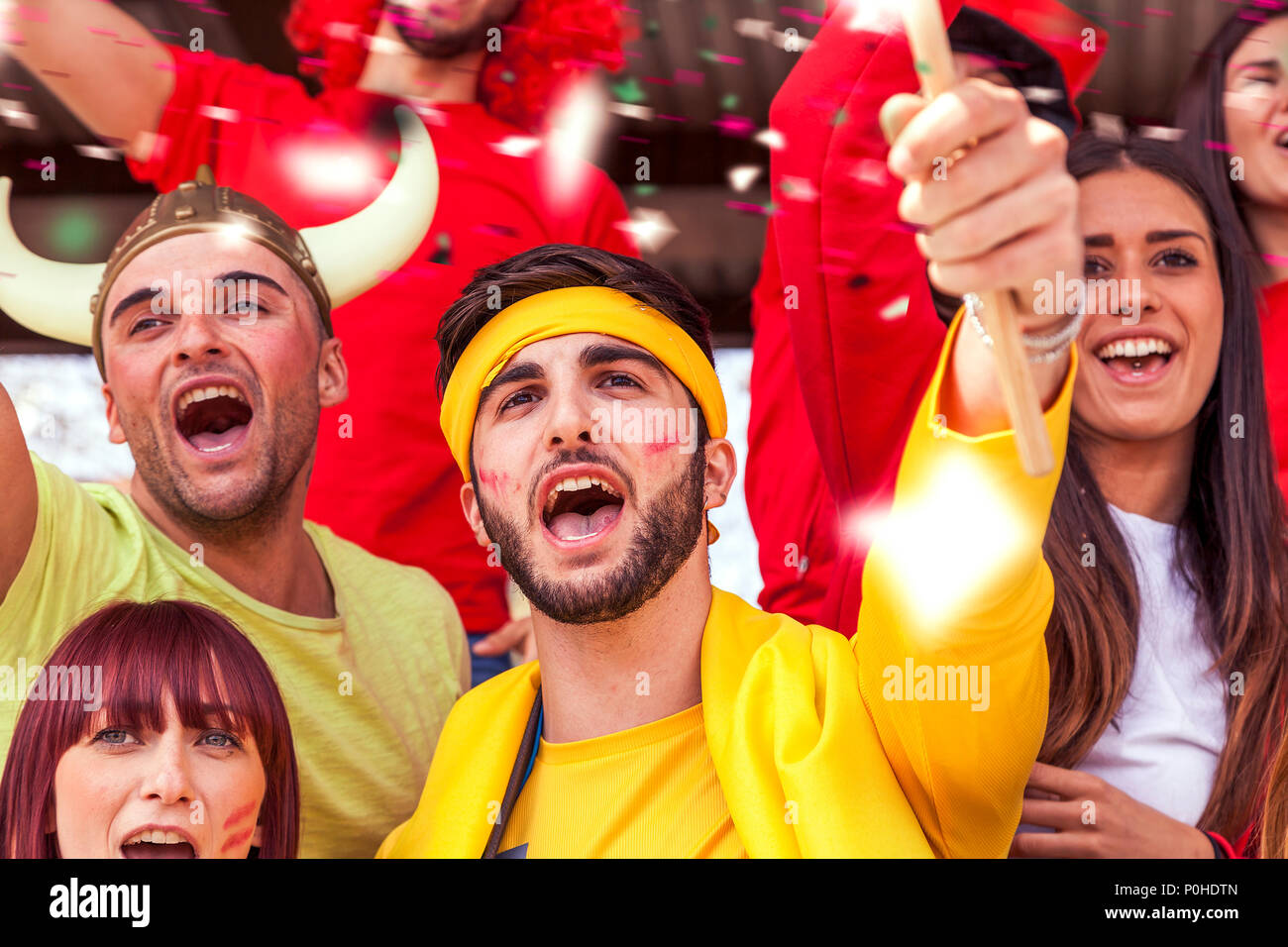 group of fans dressed in various colors watching a sports event in the stands of a stadium - Stock Image