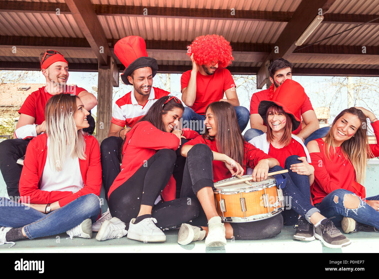 group of fans dressed in red color watching a sports event in the stands of a stadium - Stock Image