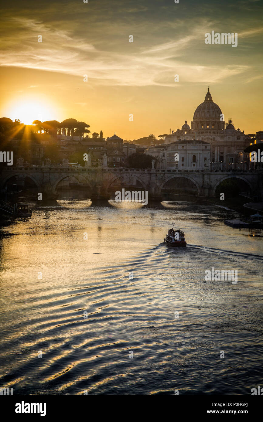 A boat travels the Tiber River in front of St. Peters Basilica in the Vatican in Rome, Italy. - Stock Image