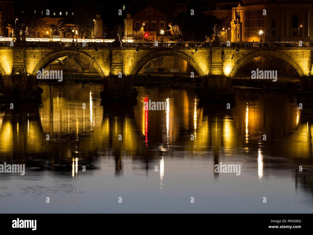 The lights from the Ponte Vittorio Emanuele II bridge reflect in the Tibor River in Rome, Italy. - Stock Image