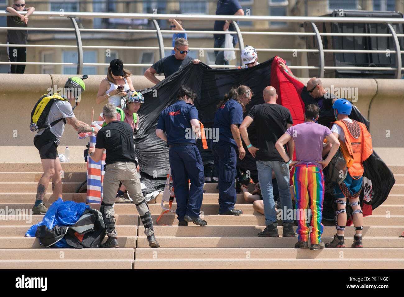 Blackpool, Lancashire, UK. 9 June 2018.  People rush to the aid of an injured base jumper who has crashed into the seaside promenade after a 400ft jump from a hired crane. A change in wind direction resulted in the canopy not fully opening which caused him to drift off course. Airgamez UK Base Jumping Championship event.  Credit:MediaWorldImages/AlamyLiveNews. Credit: MediaWorldImages/Alamy Live News - Stock Image