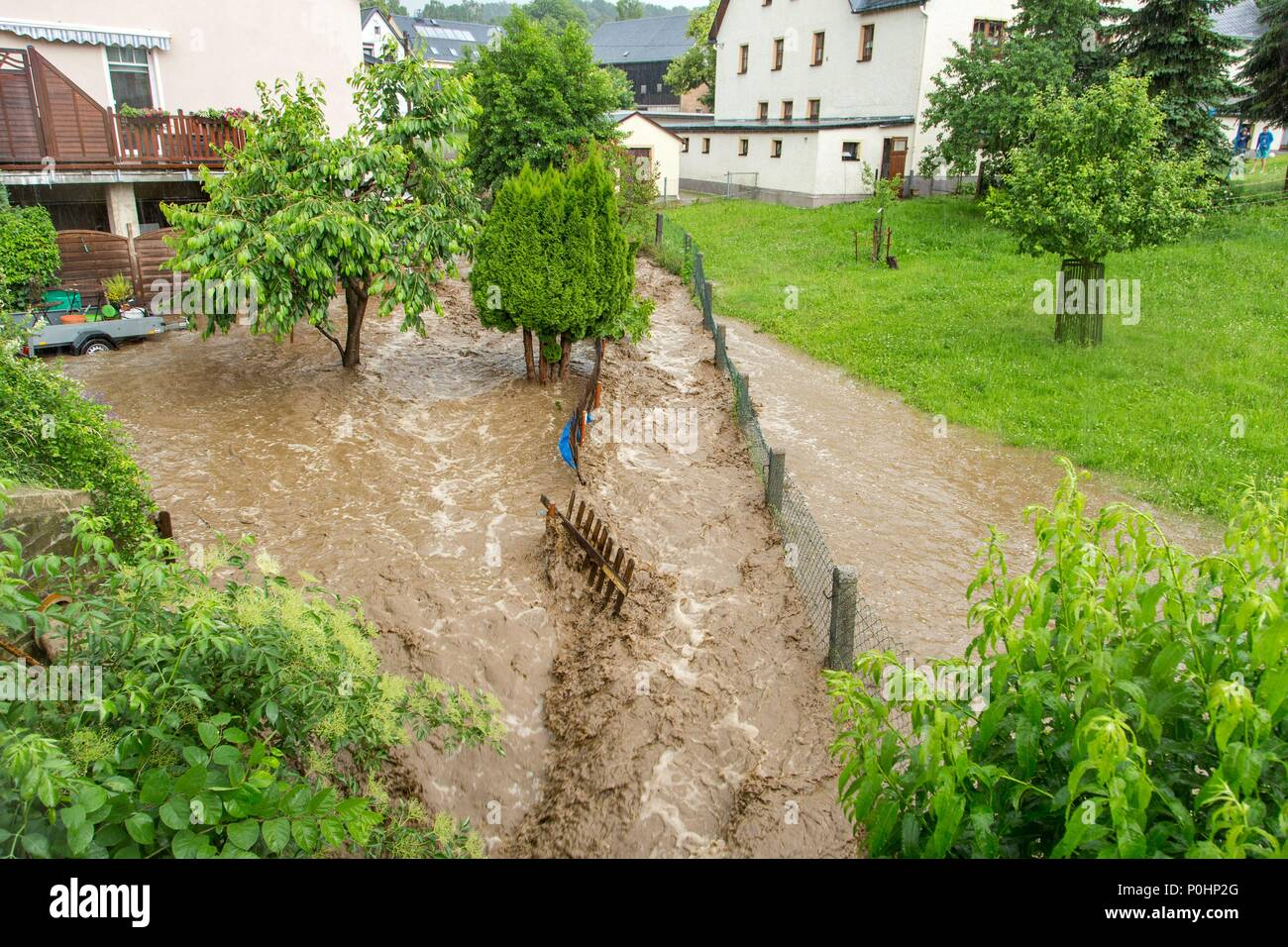 09 June 2018, Germany, Gehringswalde: Brown water masses force their way through streets after heavy rainfalls occurred in the region. Photo: Andre März/dpa-Zentralbild/dpa Stock Photo