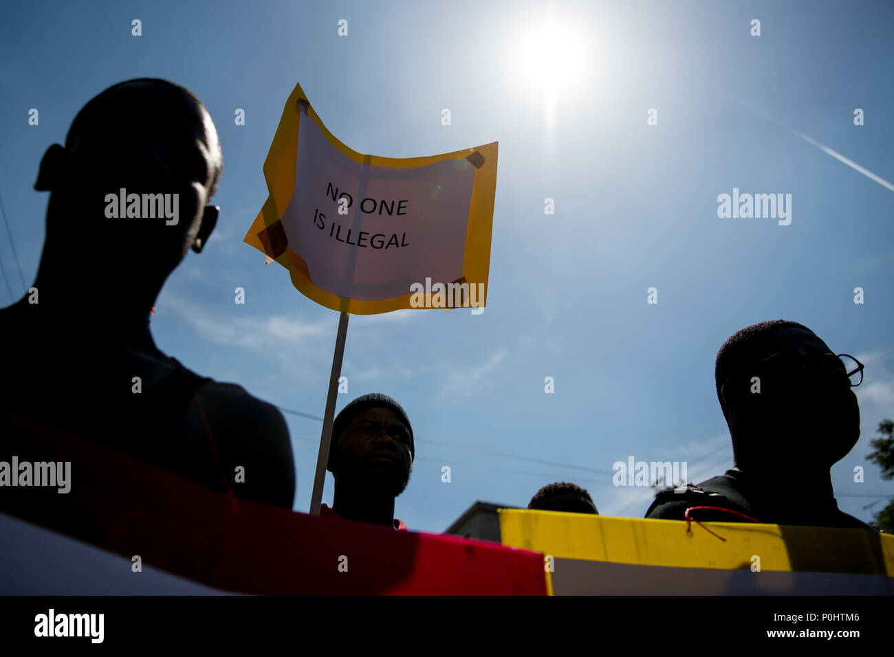 Milan, Italy - 9 June 2018: A man holds a placard  reading 'No one is illegal' during an anti-racist against the killing of Soumaila Sacko, a  29 years old Malian farm worker migrant, murdered in a shooting last Sunday in the village of San Ferdinando in the southern Italian region of Calabria. - Stock Image