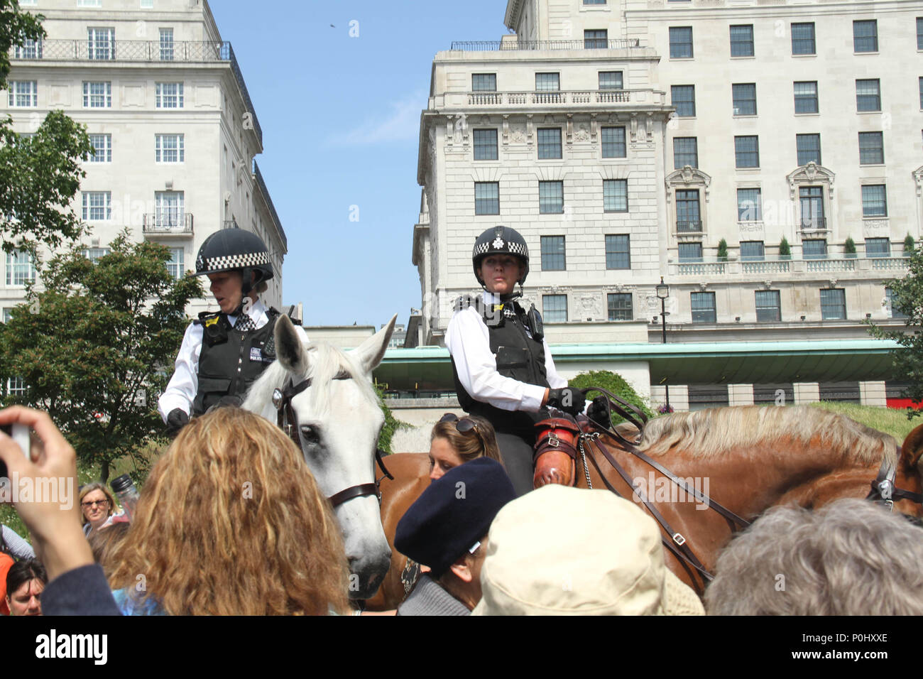 London, UK 9 June 2018: Two Police officers direct Londonners and tourist from Green STrete Station ahead of the Trooping of Colour ceremony on 9 June 2018.  Over 1400 parading soldiers, 200 horses and 400 musicians come together each June in a great display of military precision, horsemanship and fanfare to mark The Queen's official birthday. Credit: David Mbiyu/Alamy - Stock Image