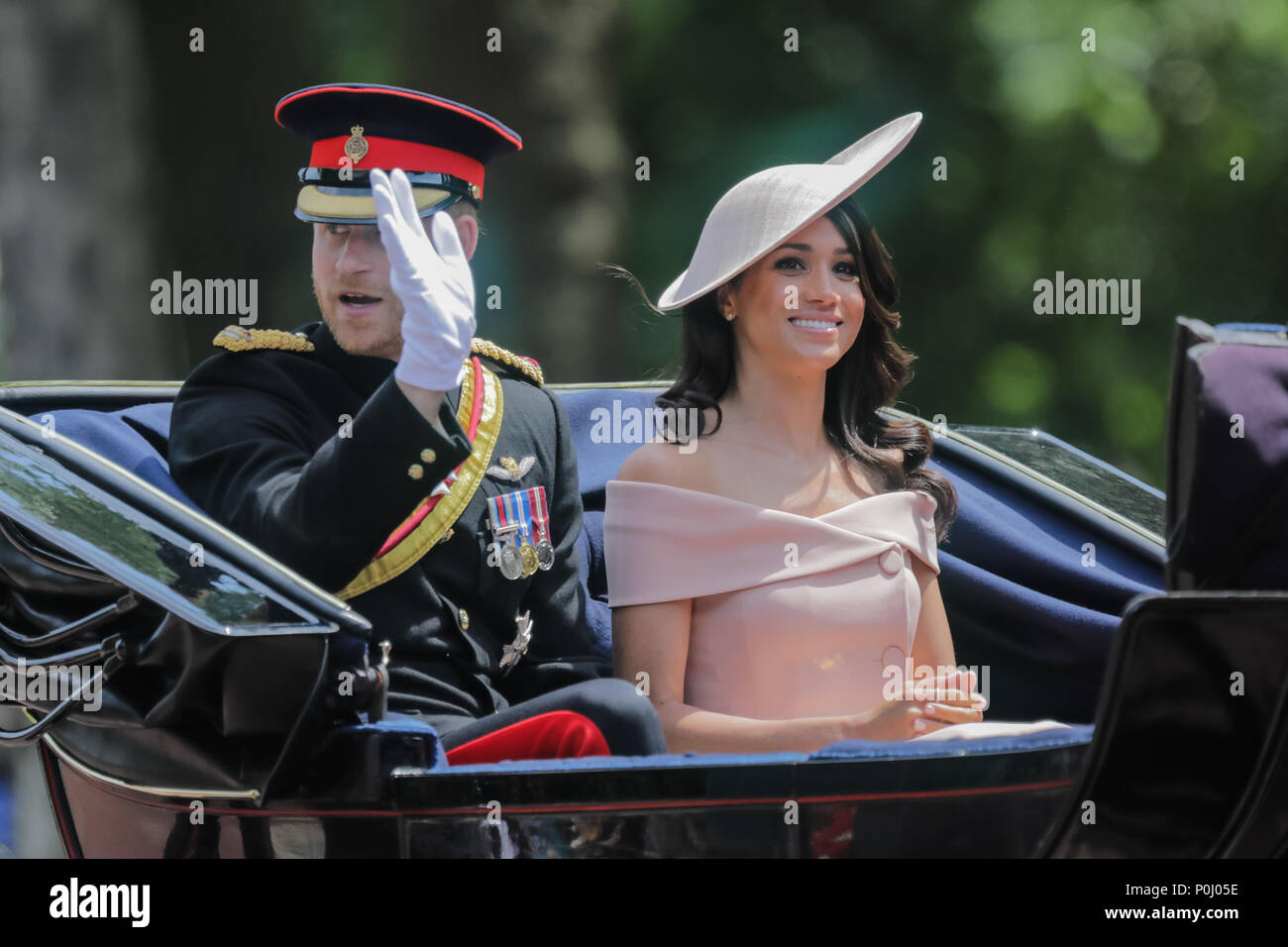 London, UK. 9th June 2018. HRH Prince Harry and his wife, Meghan, now titled the Duke and Duchdess of Sussex, ride in a horse drawn carriage in the procession along The Mall at Trooping the Colour, The Queens Birthday Parade. London.  This is Meghan, Duchess of Sussex first appearance at the procession. Credit: amanda rose/Alamy Live News Stock Photo