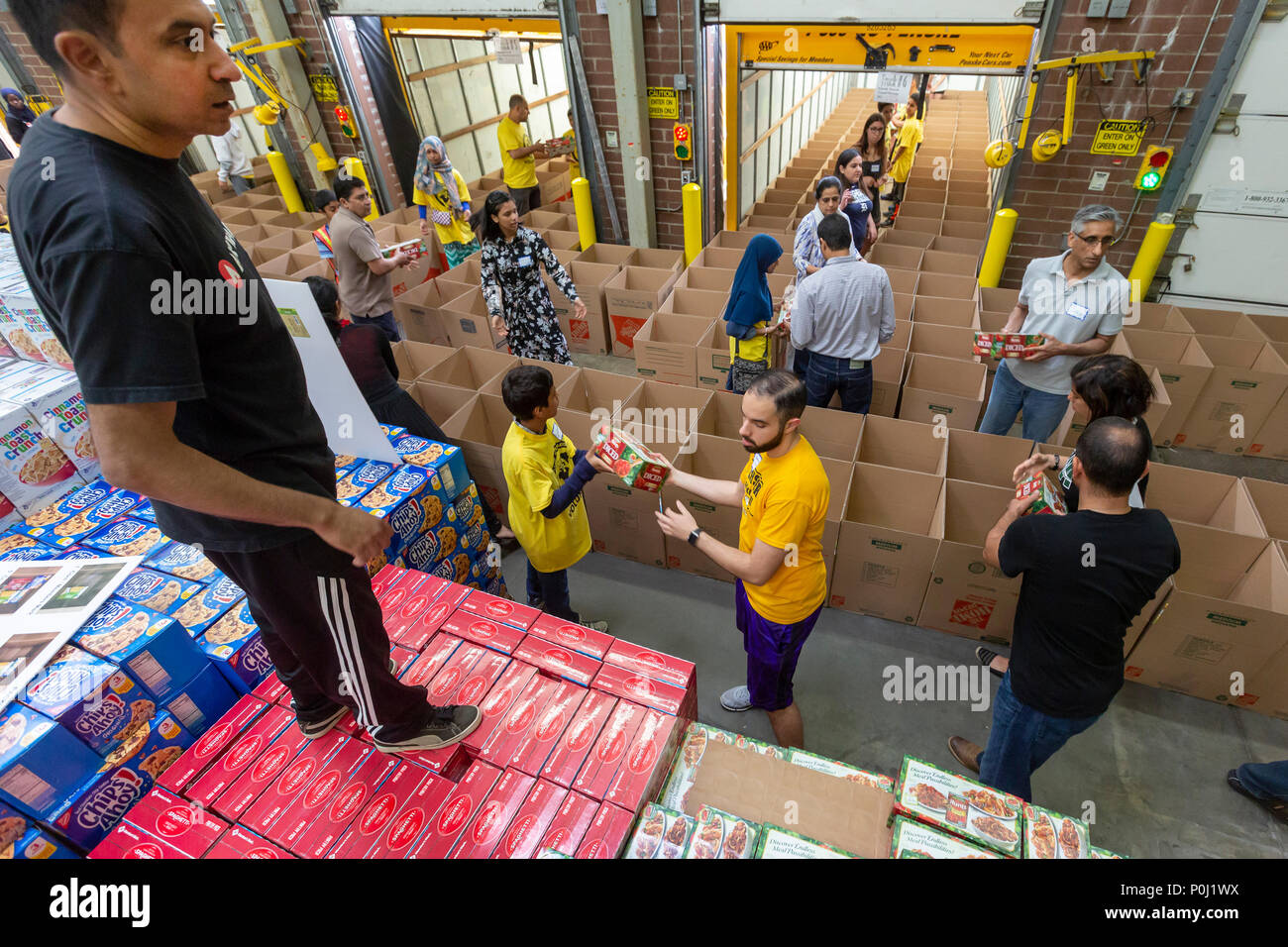 Novi, Michigan USA - 9 June 2018 - Muslim volunteers package food boxes for the less fortunate in the Detroit area during the month of Ramadan. Muslims are expected to contribute to charitable work during the month. Credit: Jim West/Alamy Live News - Stock Image