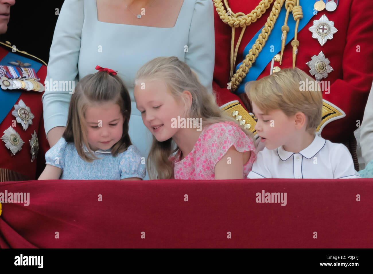 London, UK. 9th June 2018. Excited young Royals, L-R; Princess Charlotte of Cambridge, Savannah Phillips, Prince George of Cambridge enjoying the Trooping the Colour fly-past from the Buckingham Palace balcony. Credit: amanda rose/Alamy Live News - Stock Image
