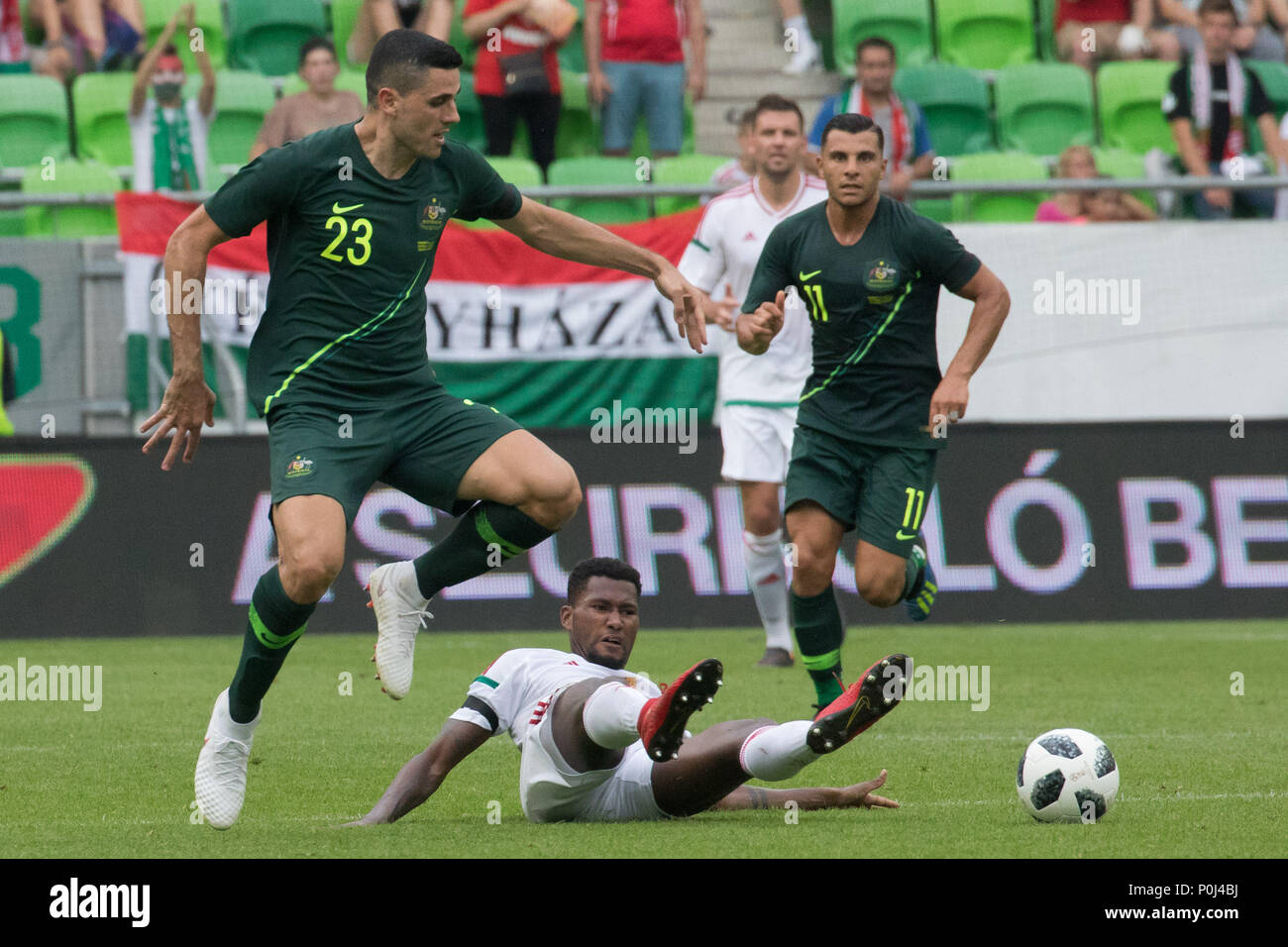 Budapest. 9th June, 2018. Tom Rogic (L) of Australia vies with Paulo Vinicius (bottom) of Hungary during the friendly match at the Groupama Arena in Budapest, Hungary on June 9, 2018. Australia won 2-1. Credit: Attila Volgyi/Xinhua/Alamy Live News - Stock Image