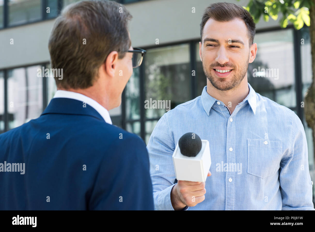 professional news reporter interviewing successful businessman with microphone - Stock Image