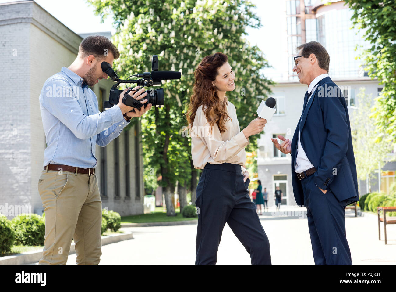 cameraman and female newscaster interviewing businessman - Stock Image