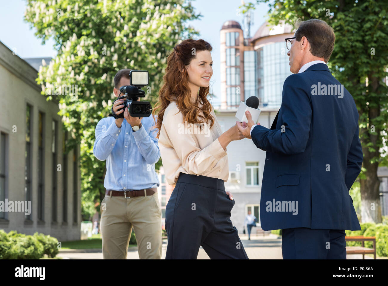 professional cameraman and news reporter interviewing businessman - Stock Image
