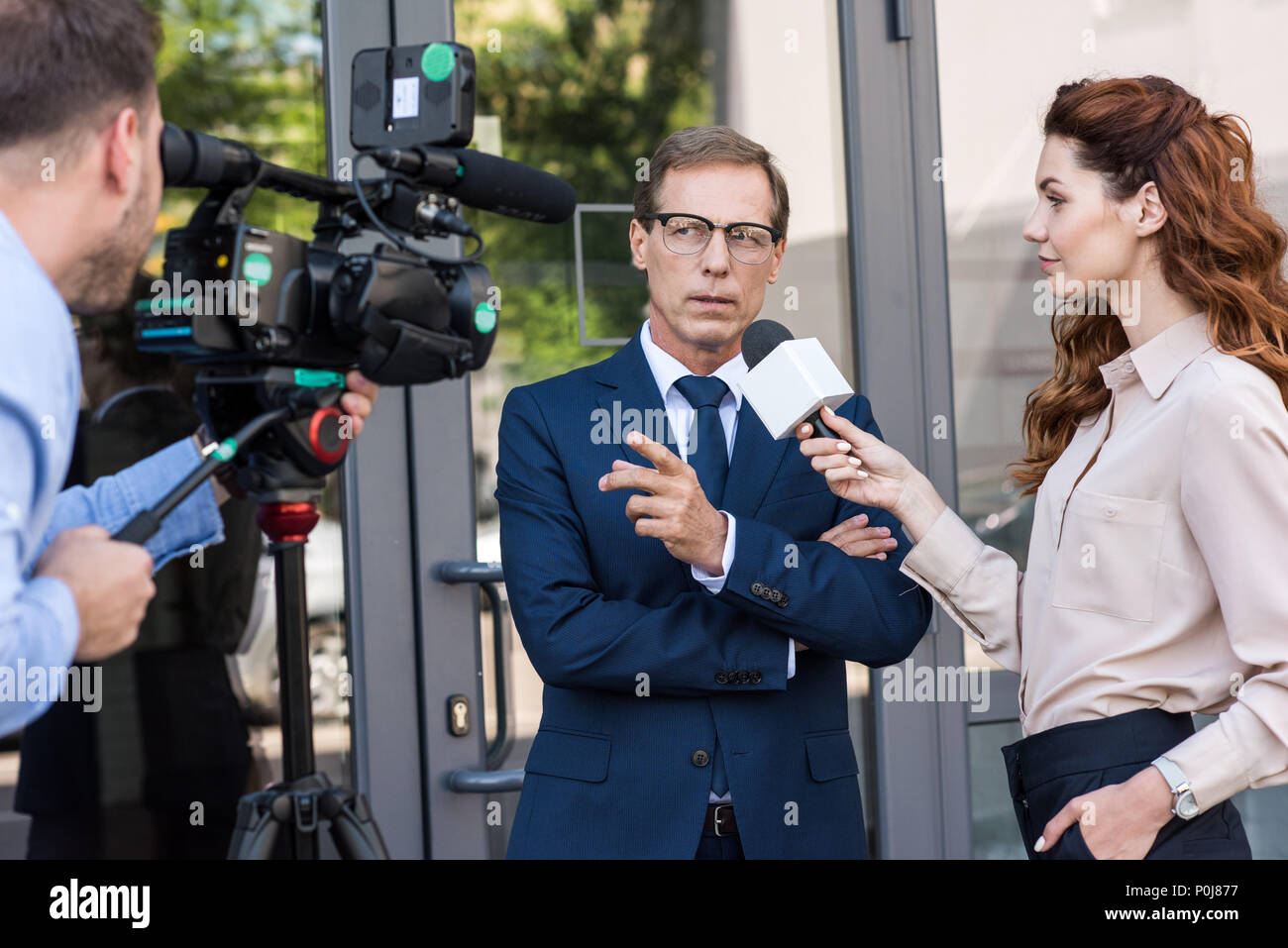 professional cameraman and news reporter talking with serious businessman - Stock Image