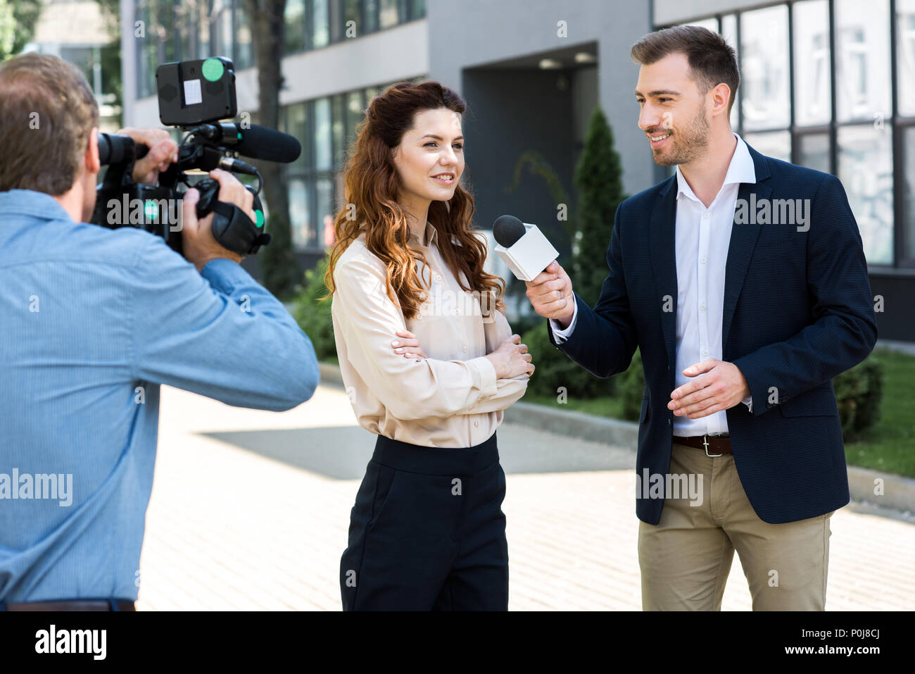 professional cameraman and male news reporter interviewing smiling businesswoman - Stock Image