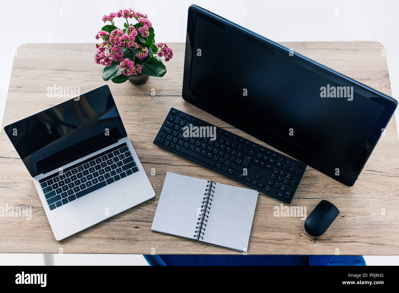 elevated view of table with flowers, empty textbook, laptop and computer with blank screens - Stock Image