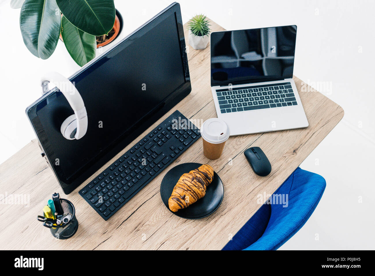 high angle view of headphones on blank computer monitor, laptop with blank screen, stationery, croissant and coffee cup on table - Stock Image