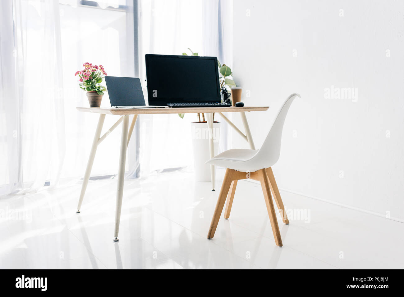 interior of workplace with chair, potted plants, laptop and computer on table - Stock Image