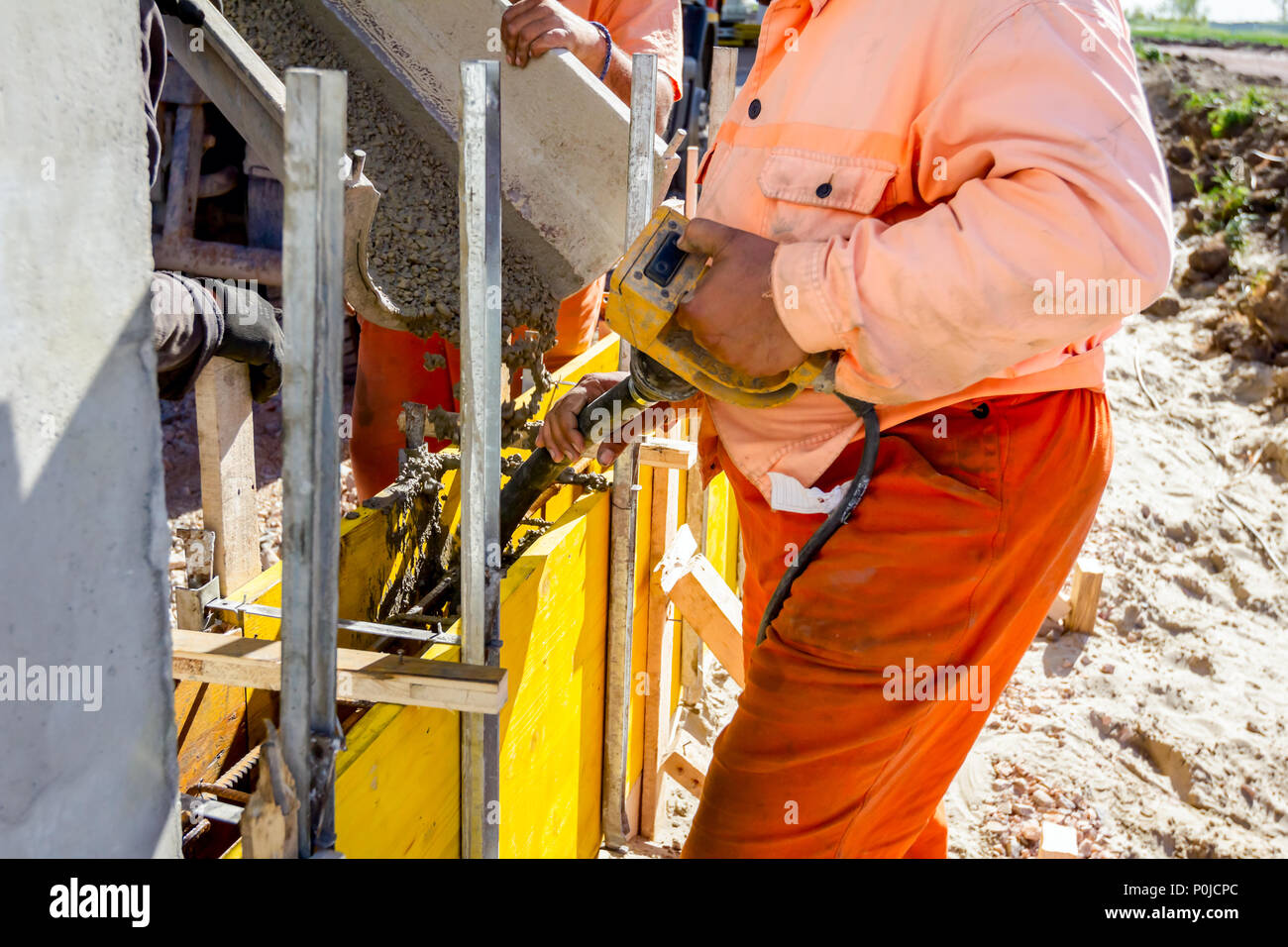Worker is using power tool, compactor, at concreting base of edifice wall. - Stock Image