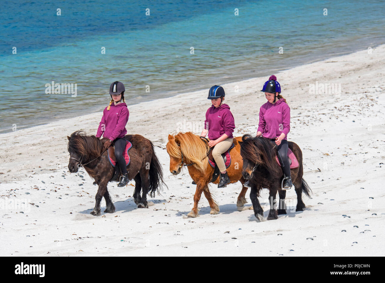 Three young girls / teenagers riding Shetland ponies on sandy beach along the Scottish coast on the Shetland Islands, Scotland, UK - Stock Image