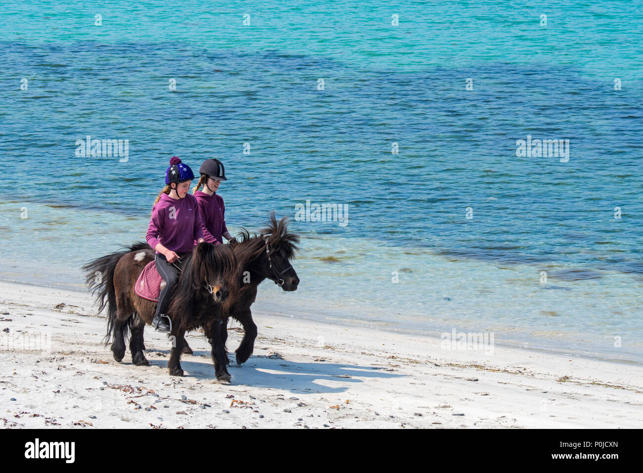 Two young girls / teenagers riding Shetland ponies on sandy beach along the Scottish coast on the Shetland Islands, Scotland, UK - Stock Image