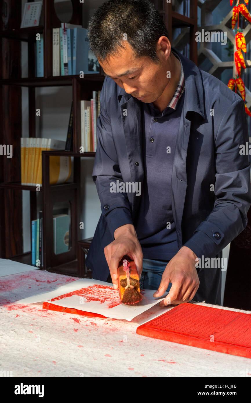 Yangzhou, Jiangsu, China.  Chinese Artist Demonstrating Block Printing Technique. - Stock Image