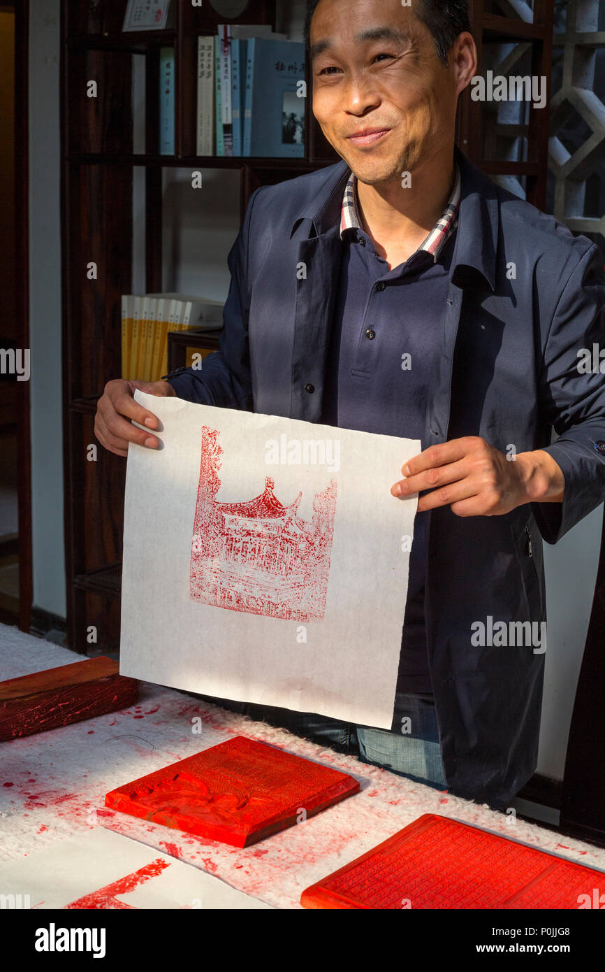 Yangzhou, Jiangsu, China.  Chinese Artist Demonstrating Block Printing Technique. - Stock Image