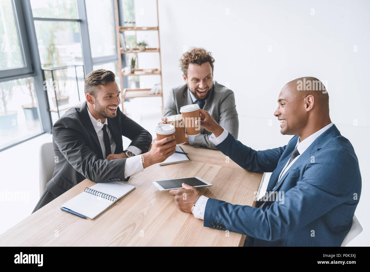 multicultural group of smiling businessmen clinking disposable cups of coffee at meeting - Stock Image