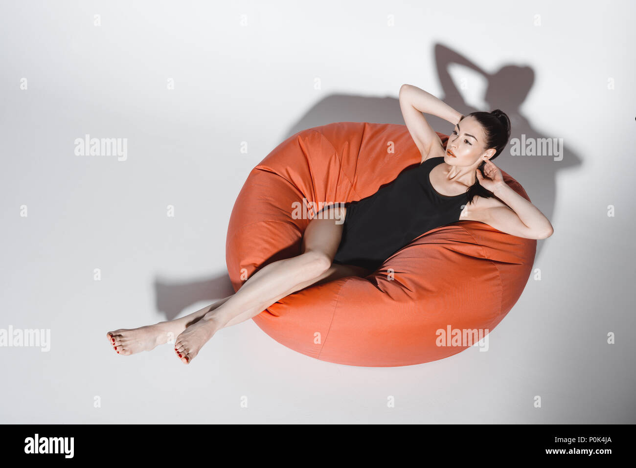 Beautiful young woman in black swimsuit resting in bean bag chair on grey - Stock Image