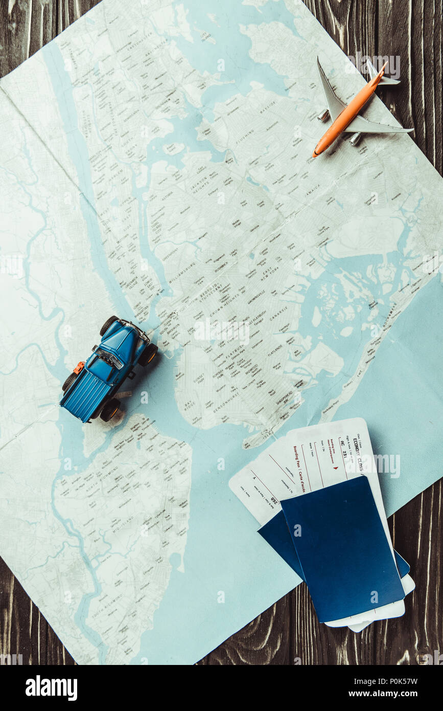 flat lay with map, toys, passports and tickets on dark wooden tabletop Stock Photo