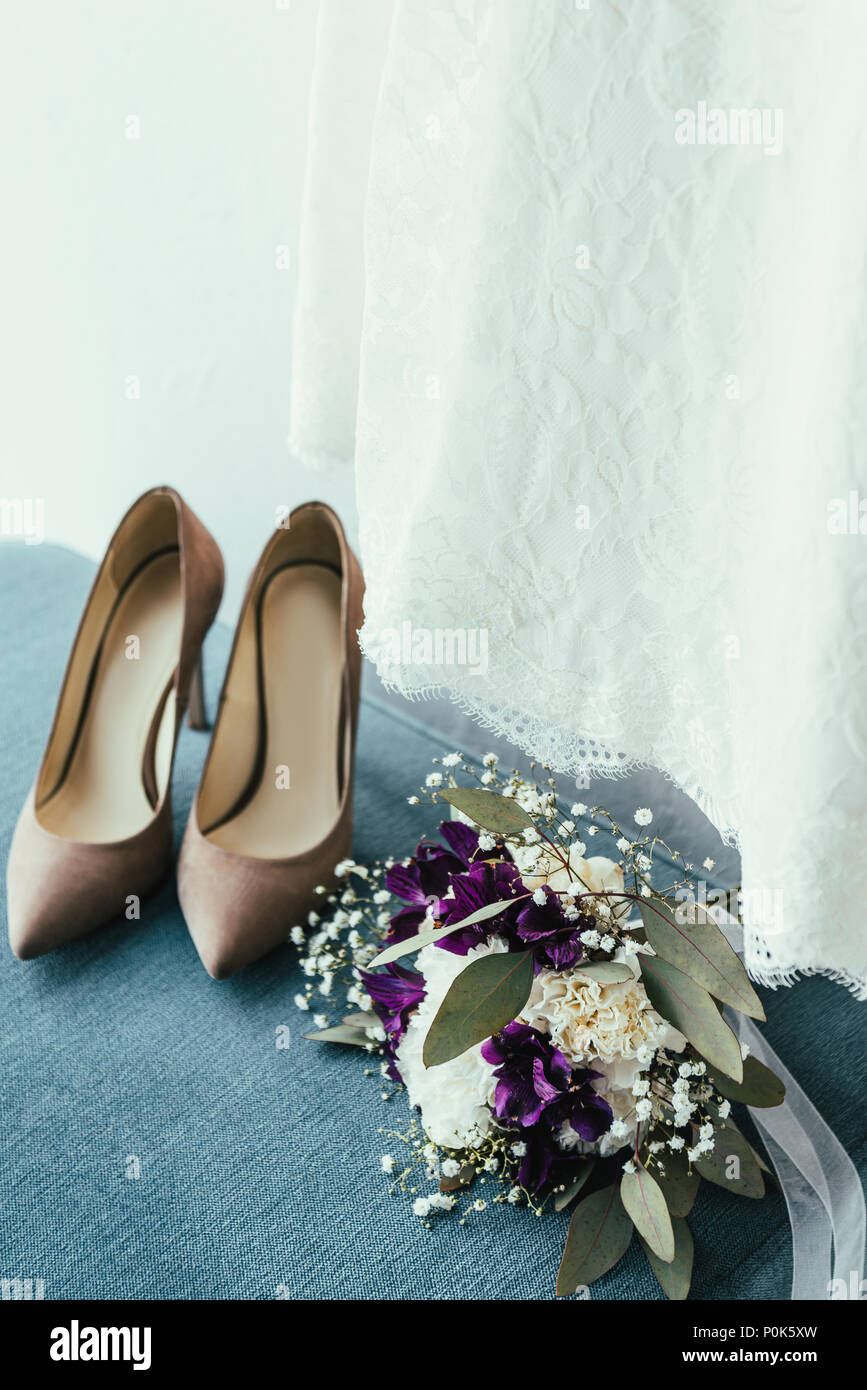 Close Up View Of Bridal Shoes Wedding Bouquet And Dress For