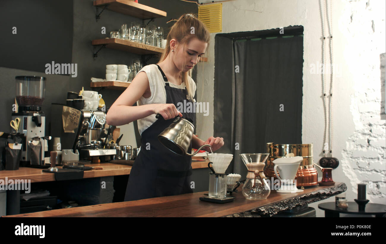 Young female barista in trendy modern cafe coffee shop pours boiling water over coffee grounds making a pour over drip coffee - Stock Image