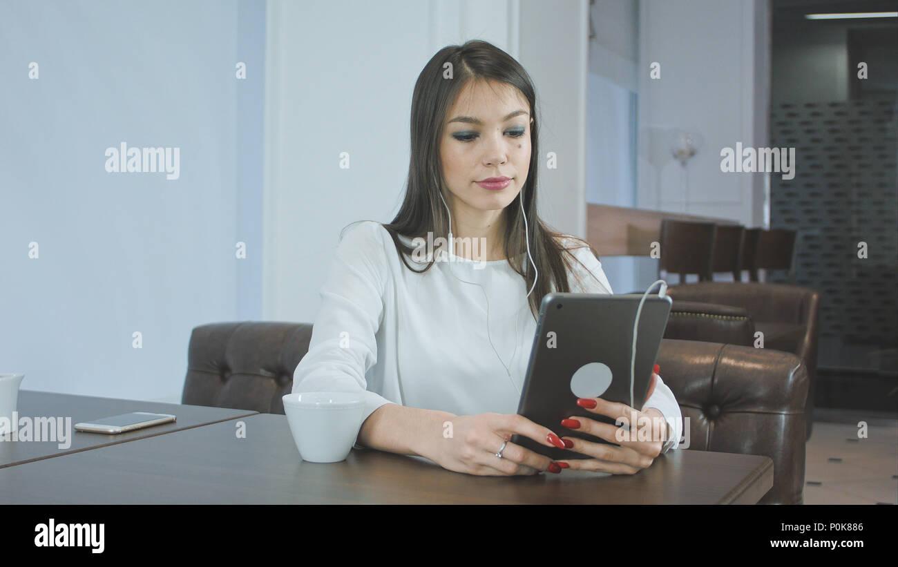 Attractive woman in earphones having video call via digital tablet - Stock Image