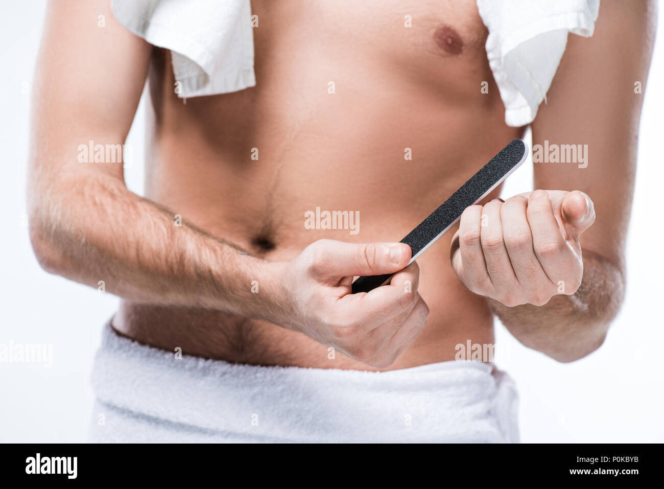 Midsection of  man with bath towel on shoulders and around waist holding nail file in hand,  isolated on white - Stock Image