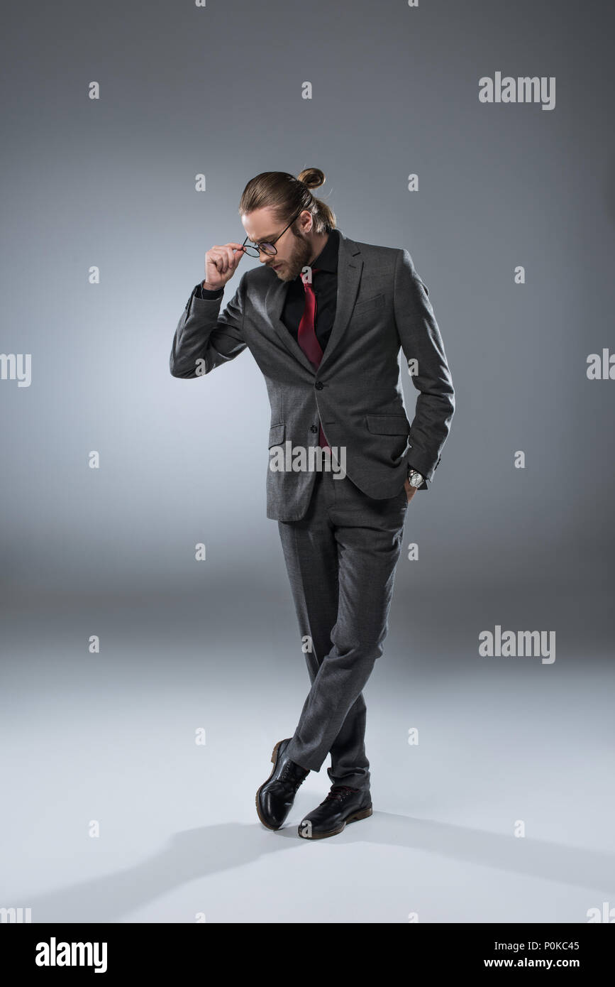 Long haired businessman in glasses looking down while standing with crossed legs, isolated on gray - Stock Image