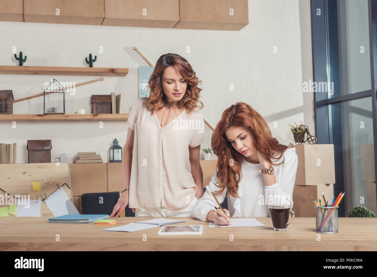 lady boss looking at manageress while she making notes - Stock Image