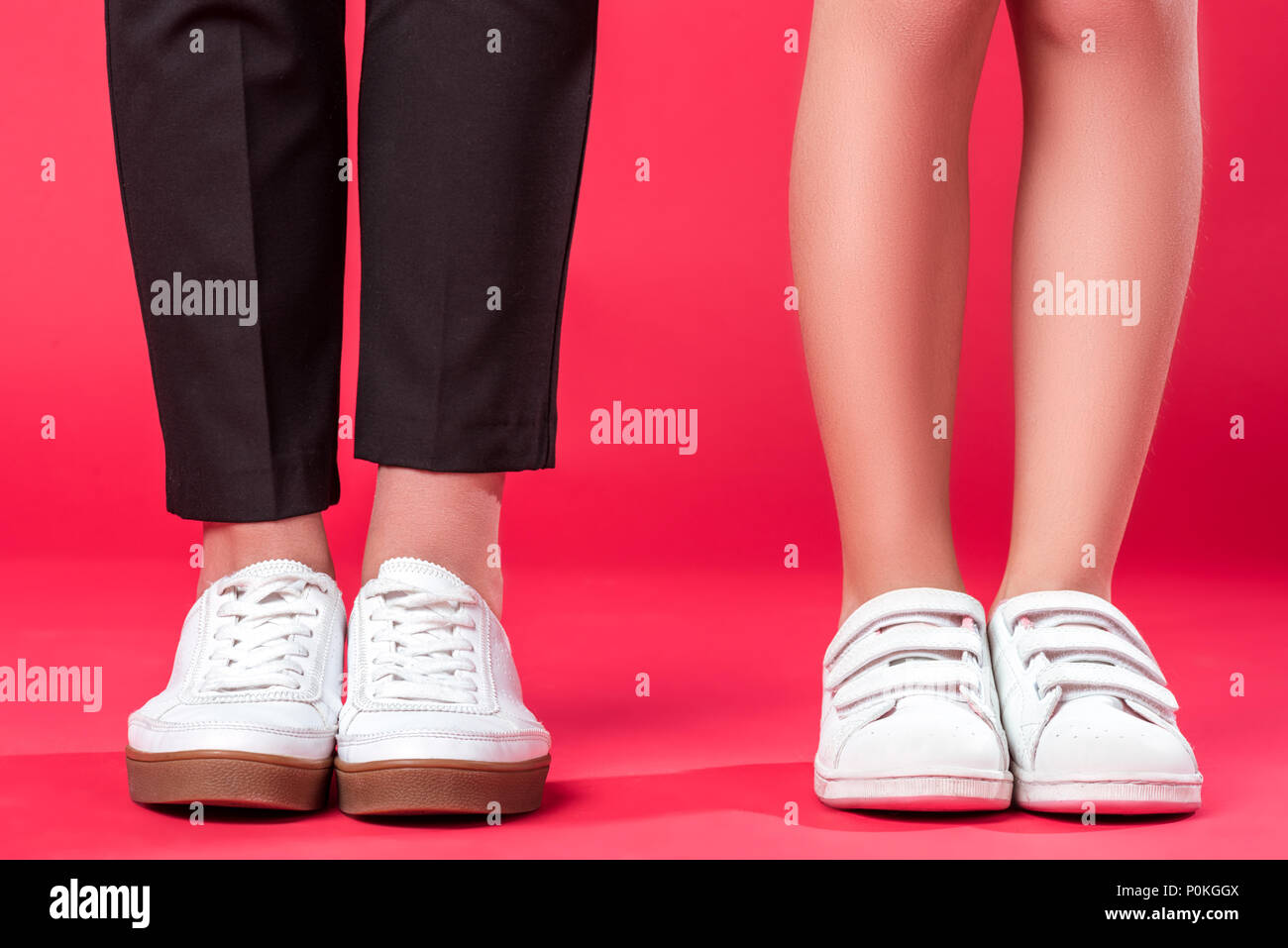 Cropped image of mother and daughter standing in gumshoes and sneakers on red - Stock Image