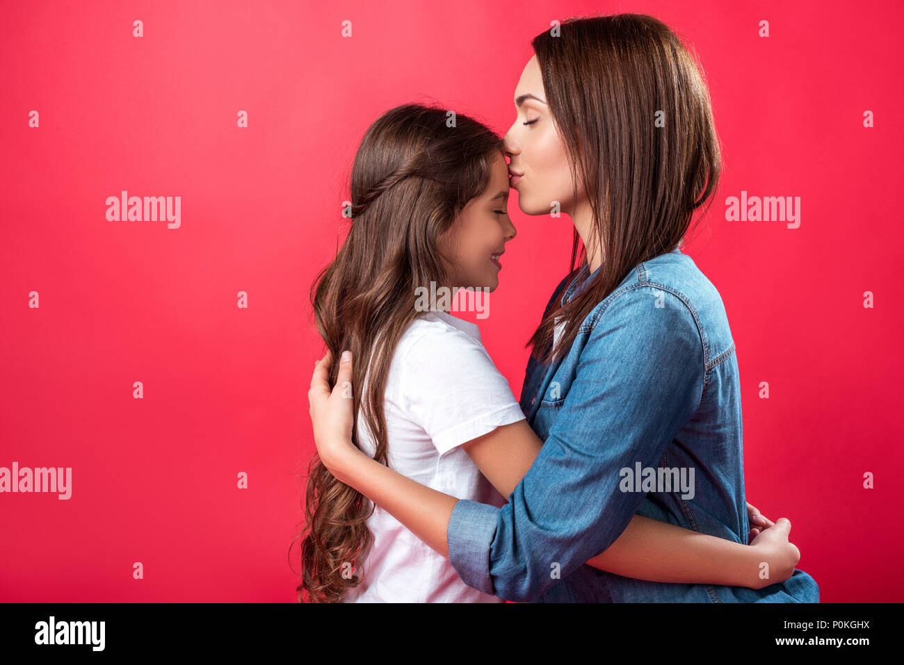Mother kissing daughter in forehead isolated on red - Stock Image