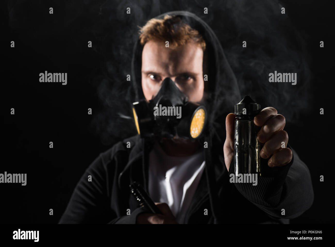 Man wearing protective filter mask smoking electronic cigarette showing E-liquid - Stock Image