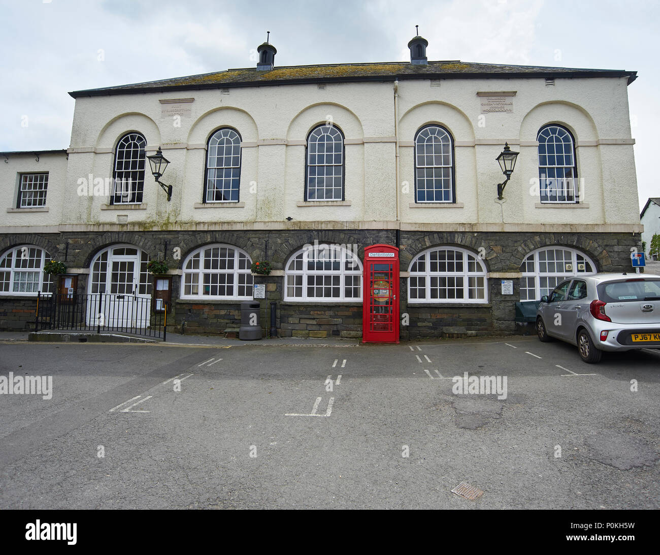 A telephone box in Hawkshead, Cumbria, UK, which now contains a defibrillator instead of a telephone - Stock Image